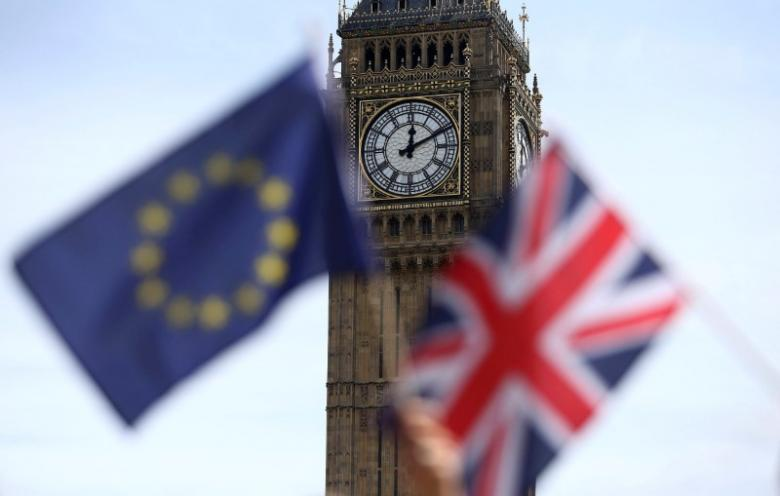 Participants hold a British Union flag and an EU flag during a pro-EU referendum event at Parliament Square in London