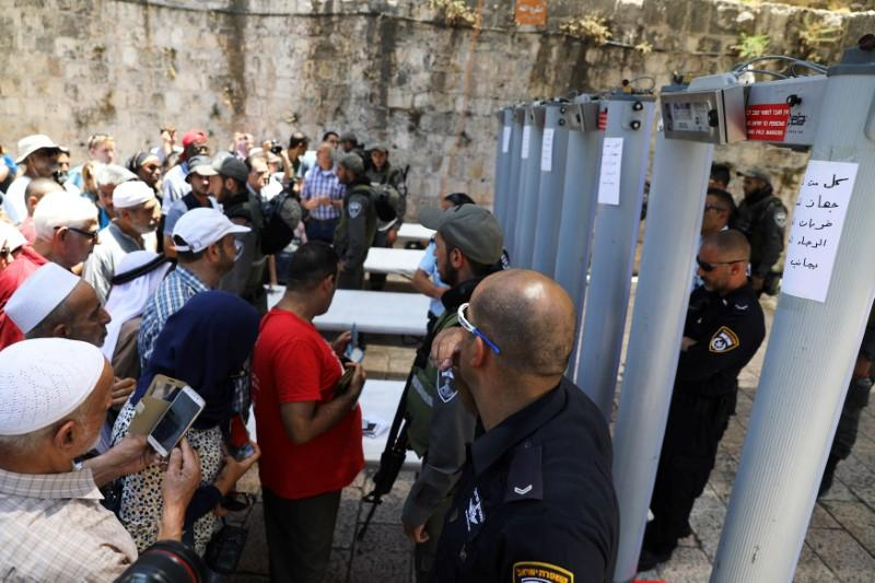 FILE PHOTO: Palestinians stand in front of Israeli policemen and newly installed metal detectors at an entrance to the compound known to Muslims as Noble Sanctuary and to Jews as Temple Mount, in Jerusalem's Old City